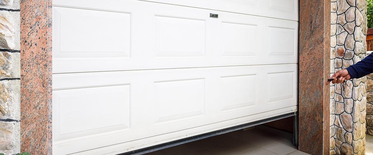 man using an automatic garage door opener on a white door