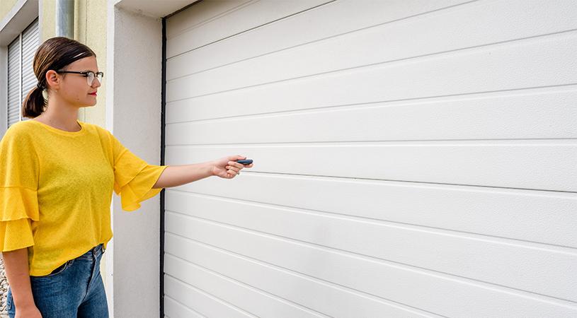 Woman pointing a garage door opener at a white garage door